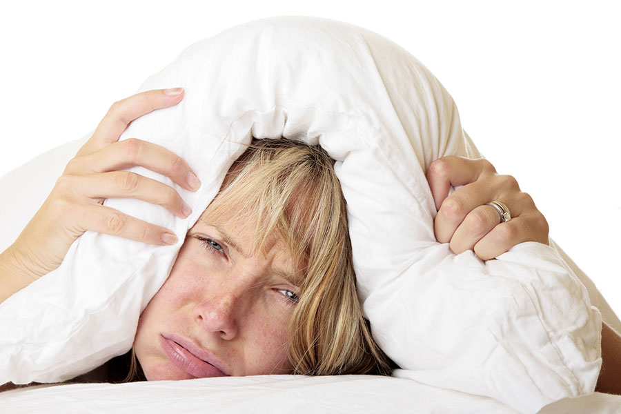 woman with head under pillow cannot sleep insomnia