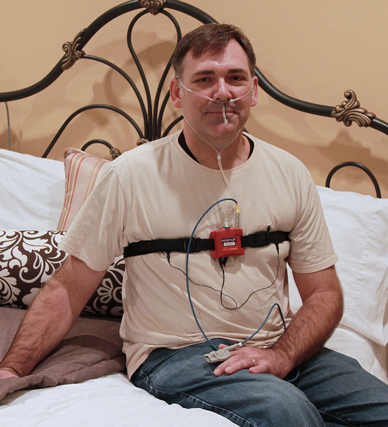 man with home sleep testing device sitting on a bed