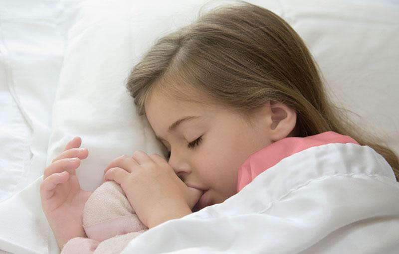 little girl sleeping sucking her thumb