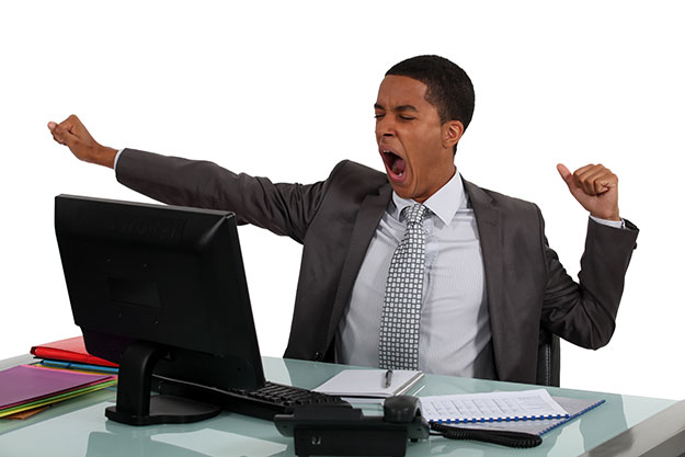 black business man yawning in front of his computer monitor